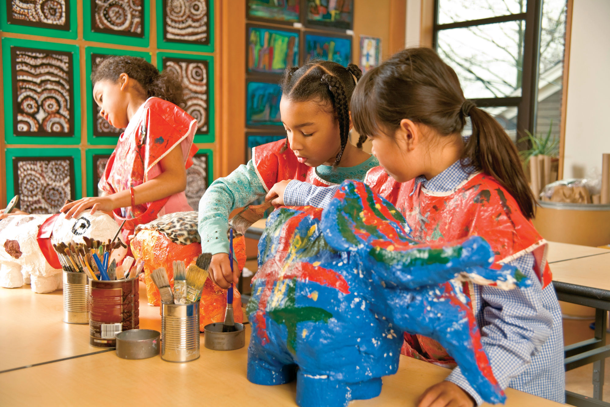 Group of children painting with coloring paints in art class.