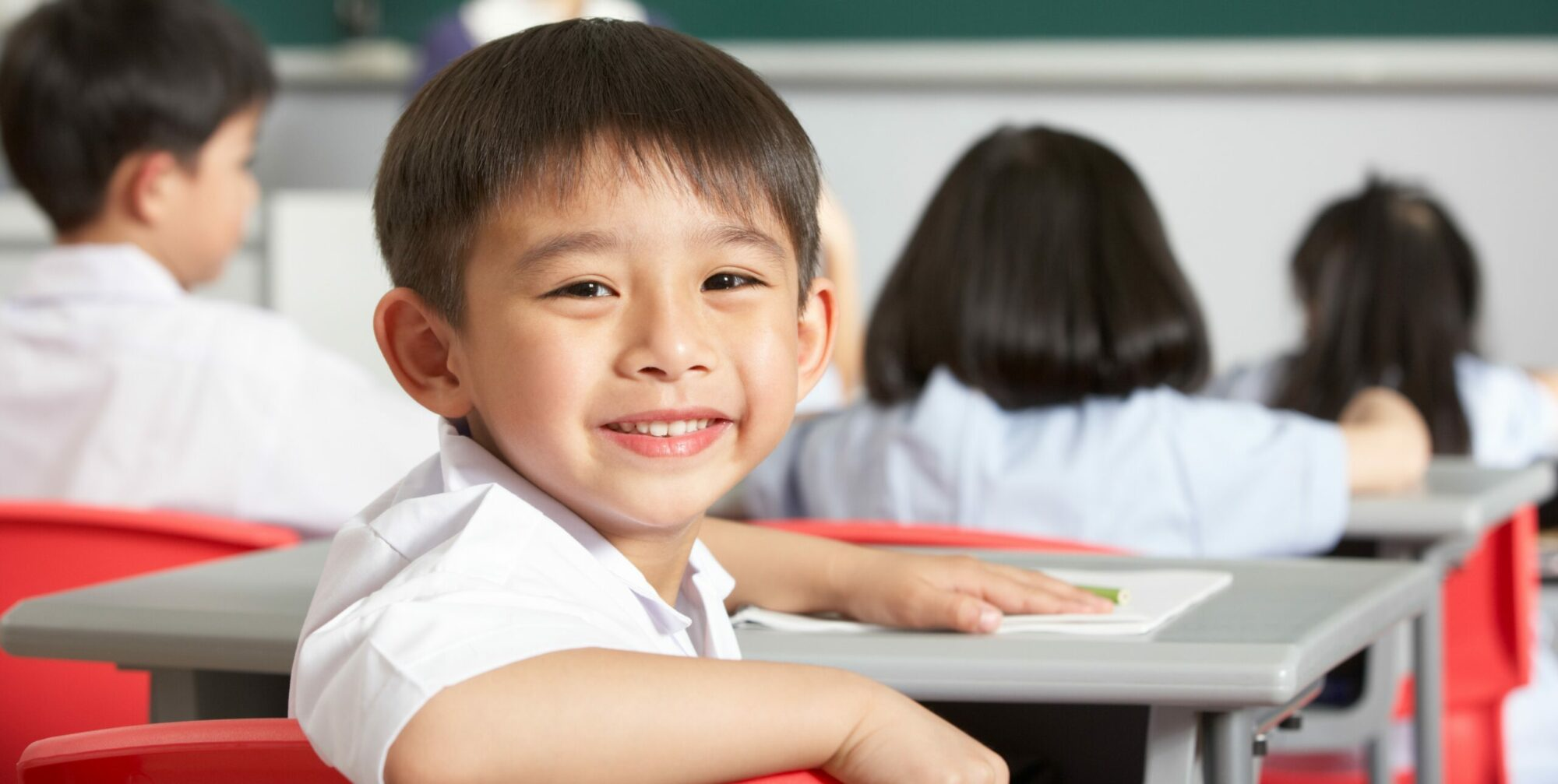 Young smiling child in classroom sitting at a desk with other students.
