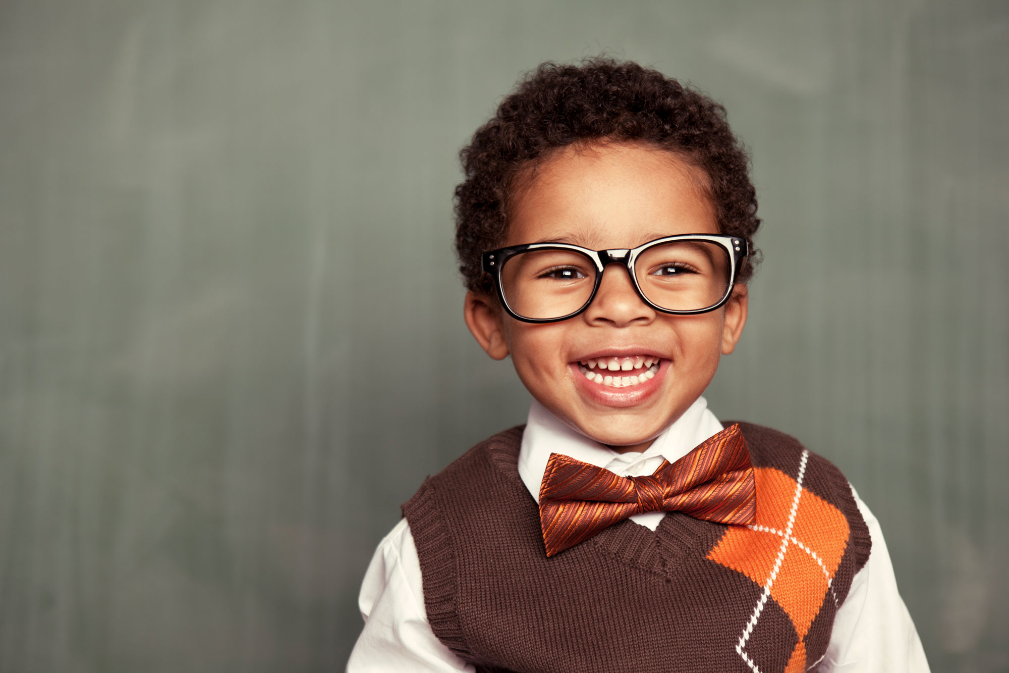 Happy toddler smiling wearing glasses and a bow tie.