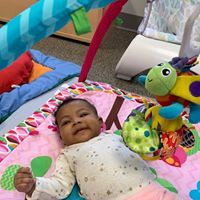 Smiling baby with colorful stuffed animals.