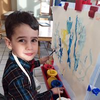 Young smiling child painting on a canvas in art class.