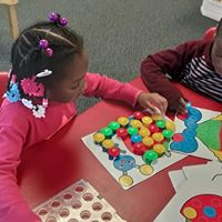 Young student playing with learning materials in a classroom.