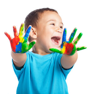 Happy child with painted hands smiling at the camera.