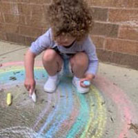 Young child outside playing with chalk.